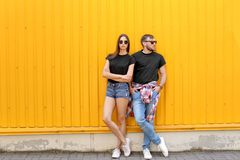 Young couple wearing black t-shirts near color wall. On street stock image