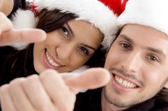 Young couple wearing christmas hat and looking. Close up view of young couple wearing christmas hat and looking at camera against white background Royalty Free Stock Images