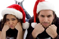 Young couple wearing christmas hat and looking. Close up view of young couple wearing christmas hat and looking at camera against white background Royalty Free Stock Photo