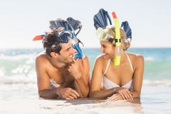 Young couple wearing diving mask lying on beach. Happy young couple wearing diving mask lying on beach Royalty Free Stock Photos
