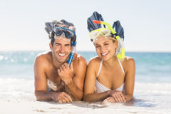 Young couple wearing diving mask lying on beach. Portrait of happy young couple wearing diving mask lying on beach Stock Images