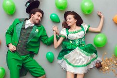 Young couple in festive costumes saint patrick`s day top view among balloons. Young couple wearing festive costumes saint patrick`s day top view  on grey lying Stock Image