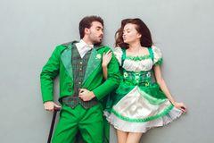 Young couple in festive costumes saint patrick`s day top view kissing. Young couple wearing festive costumes saint patrick`s day top view  on grey turn towards Stock Image