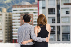 Young couple wearing formal clothes standing on rooftop, arms around each other as seen from behind, looking out to city Royalty Free Stock Photos