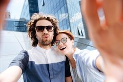 Young couple wearing glasses laughing while making selfie. Laughing couple. Young stylish modern couple wearing glasses laughing while making selfie for stock image
