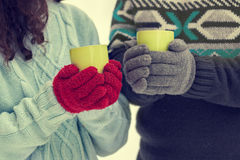 Young couple wearing gloves hold cups with tea Royalty Free Stock Image