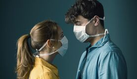 Young couple wearing a protective face mask