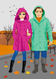Young couple wearing raincoats standing in park in autumn Royalty Free Stock Images