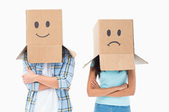 Young couple wearing sad face boxes over head Stock Images