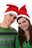 Young couple wearing Santa hats isolated on white Royalty Free Stock Images