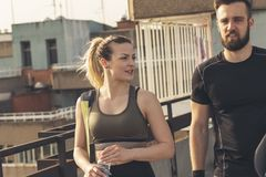 Couple going to a gym. Young couple wearing sportswear, carrying a gym bag and a yoga mat, going to a gym royalty free stock image