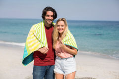 Young couple wearing towel while standing at beach Stock Photos