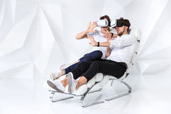 A young couple wearing VR headsets sitting on white chair in a room with white walls and floors Royalty Free Stock Images