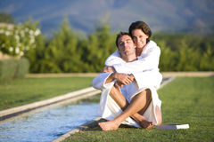 Young couple wearing white bath robes embracing outdoors by pool, smiling, portrait Stock Image