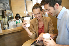Young couple websurfing with tablet and drinking coffee Stock Photo