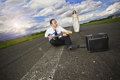 Young couple before wedding. Sitting on the road with a guitar stock photos