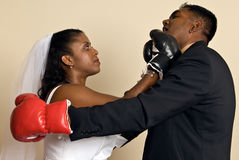 Young couple in wedding attire with boxing gloves. A young ethnic couple wedding attire wearing boxing gloves. She connects with a right hook, showing her Stock Photos