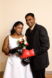 Young couple in wedding attire wearing boxing gloves. A young ethnic couple pose in wedding attire wearing boxing gloves Royalty Free Stock Images