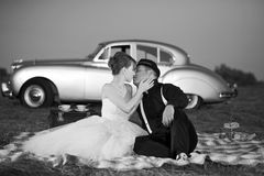 Young couple. Young wedding couple kissing in front of old car Royalty Free Stock Image