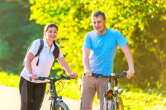 Young couple on the weekend to ride a bike. In the park Stock Photo