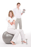 Young couple with weights and fitness ball Royalty Free Stock Photo
