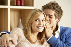 Young Couple Whispering To Each Other. Sat At Home Stock Images