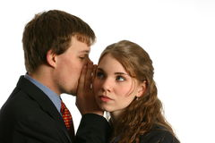 Young Couple whispering at work. Young woman in listens intently to gossip whispered in his ear by a male co-worker isolated on white space Royalty Free Stock Images