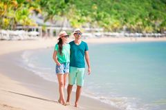 Young couple on white beach. Happy family on honeymoon vacation. Young couple on white beach during summer vacation. Happy lovers enjoy their honeymoon at exotic Royalty Free Stock Photography