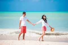Young couple on white beach. Happy family on honeymoon vacation. Young couple on white beach during summer vacation. Happy lovers enjoy their honeymoon at exotic Stock Image