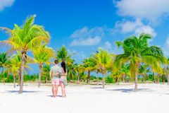 Young couple on white beach outdoors. Happy family enjoy their honeymoon in palm grove. Young couple on white beach during summer vacation. Happy lovers enjoy Royalty Free Stock Photo