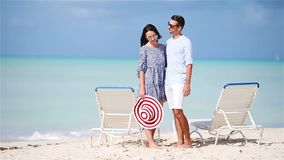 Young couple on white beach during summer vacation. Happy family enjoy their honeymoon. Young couple on white beach during summer vacation. Happy lovers enjoy stock video