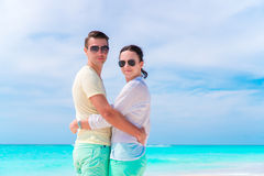 Young couple on white beach during summer vacation. Happy lovers enjoy their honeymoon Stock Images