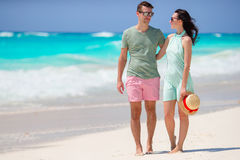 Young couple on white beach during summer vacation. Happy lovers enjoy their honeymoon. Royalty Free Stock Image