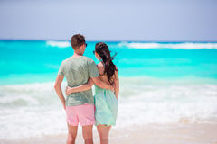 Young couple on white beach during summer vacation. Happy lovers enjoy their honeymoon. Royalty Free Stock Photography