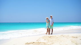 Young couple on white beach during summer vacation. Happy lovers enjoy their honeymoon. Young couple on white beach during summer vacation. Happy lovers enjoy stock footage