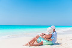Young couple on white beach during summer vacation. Happy lovers enjoy their honeymoon Stock Photos