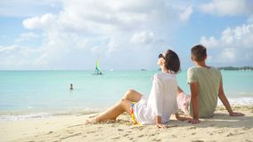 Young couple on tropical beach with white sand and turquoise ocean water at Antigua island in Caribbean. Young couple on white beach during summer vacation stock footage