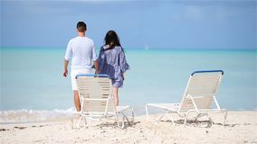 Young couple on white beach during summer vacation. Happy family enjoy their honeymoon. Young couple on white beach during summer vacation. Happy lovers enjoy stock video footage