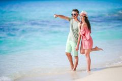 Young couple on white beach during summer vacation. Happy family enjoy their honeymoon. Young couple on white beach during summer vacation. Happy lovers enjoy Stock Images