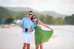 Young couple on white beach. Happy family on honeymoon vacation. Young couple on white beach during summer vacation. Happy lovers enjoy their honeymoon at exotic Stock Photos