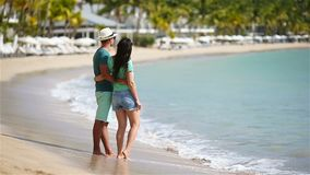 Young couple on white beach during summer vacation. Happy family enjoy their honeymoon. Young couple on white beach during summer vacation. Happy lovers enjoy stock footage