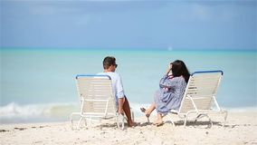 Young family on white beach during summer vacation. Young couple on white beach during summer vacation. Happy lovers enjoy their honeymoon at exotic island stock video footage