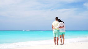 Young couple on white beach during summer vacation. Happy lovers enjoy their honeymoon. SLOW MOTION VIDEO. Young couple on white beach during summer vacation stock footage