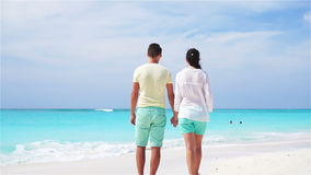 Young couple on white beach during summer vacation. Happy lovers enjoy their honeymoon. SLOW MOTION VIDEO. Young couple on white beach during summer vacation stock video footage