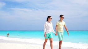 Young couple on white beach during summer vacation. Happy lovers enjoy their honeymoon. SLOW MOTION VIDEO. Young couple on white beach during summer vacation stock video