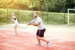 Couple playing tennis. Young couple in white sports wear playing tennis on the tennis court outdoors royalty free stock photography