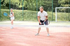 Couple playing tennis. Young couple in white sports wear playing tennis on the tennis court outdoors royalty free stock photo