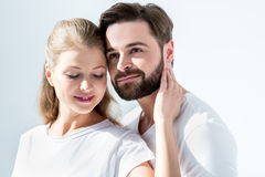Young couple in white t-shirts standing embracing on grey Royalty Free Stock Photo