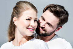 Young couple in white t-shirts standing embracing on grey Royalty Free Stock Photos