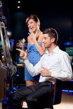 Young couple winning at the slot machine. Young couple watching exiting, winning at the slot machine Royalty Free Stock Photo